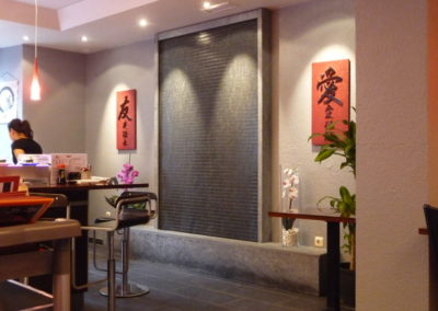Stone waterwall in running sushi restaurant